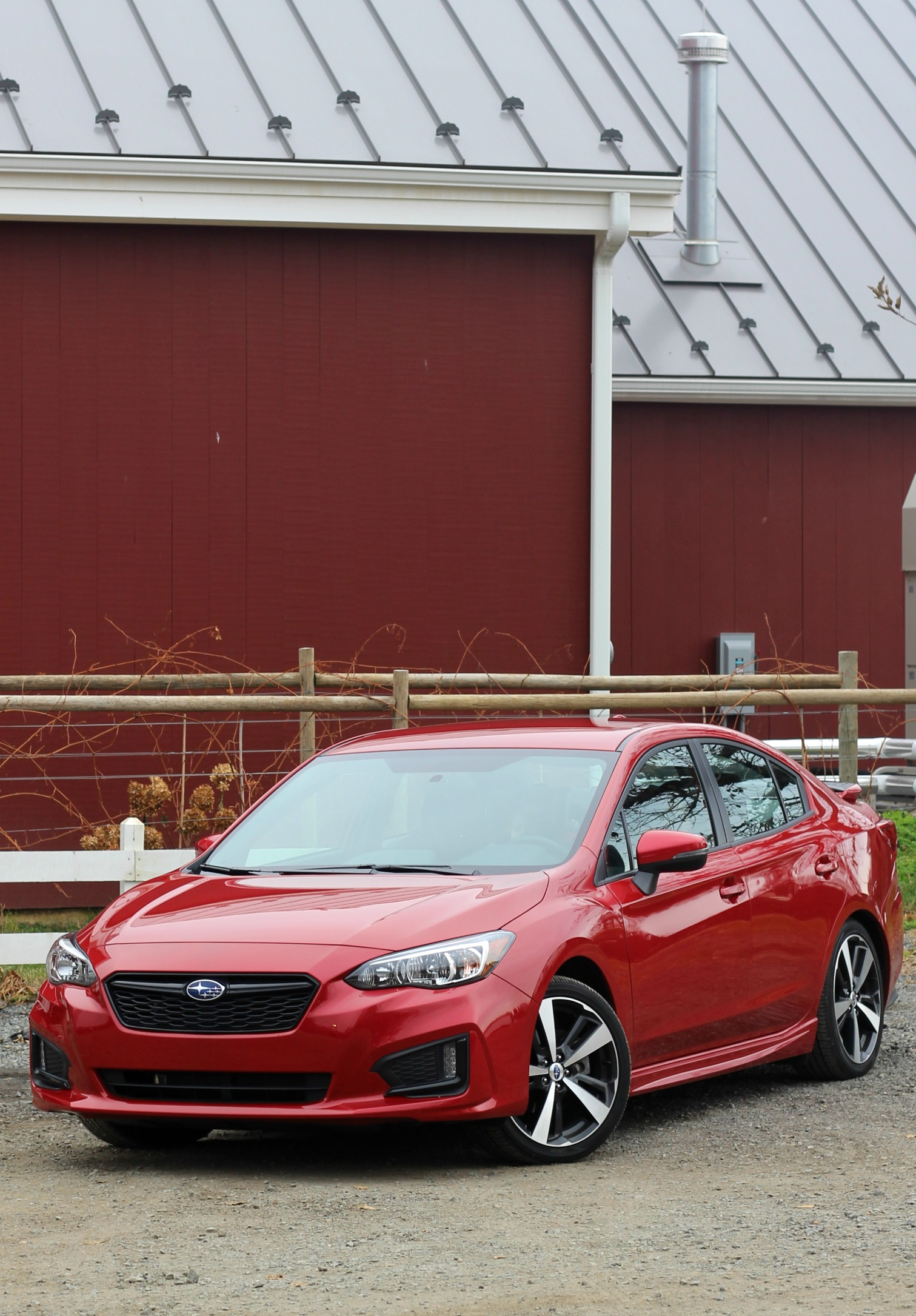 2017red  Subaru Impreza parked next to a barn and wood fence